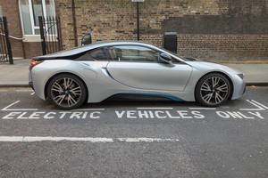 Sports car parked at parking spot for electric vehicles with charging station