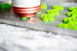 Spritz cookie press in a baking sheet
