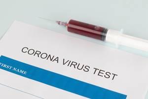 Spritze mit Blutprobe neben einem Corona Virus Test auf einem weißem Tisch