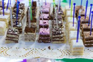 Square pieces of different cakes displayed in rows and served with multicoloured plastic cake picks