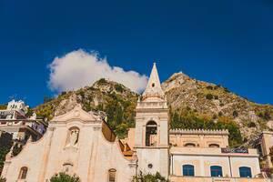 St. Joseph Kirche auf dem Piazza IX Aprile in Taormina, Sizilien mit Bergen im Hintergrund