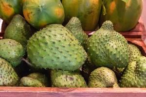 Stachelannone und Mango-Früchte in Holzkisten