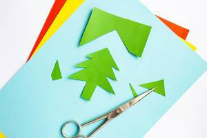 Stack of colorful craft papers with green christmas tree and scissors laying on top with white background