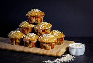 Stack of Oatmeal Muffins on a Wooden Cutting Board on Dark Background