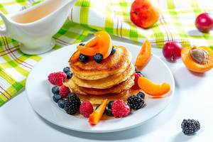 Stack of pancakes with fruit blueberries, raspberries, mulberry, apricot pieces and honey (Flip 2019)