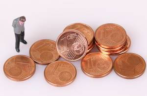 Stacks of One Euro cent coins with businessman on white background