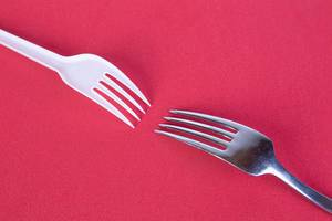 Stainless steel and plastic fork on red background