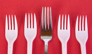 Stainless steel and plastic forks on red background