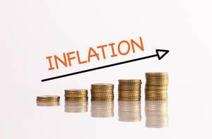 Stapel aus goldenen Münzen mit Pfeil und dem Text Inflation