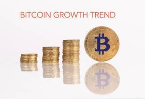 """Stapel aus Goldmünzen mit goldener Bitcoinmünze und dem Text """"Bitcoin Growth Trend"""" (Bitcoin Wachstumstrend)"""