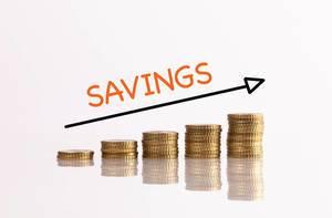 """Stapel aus Münzen mit Pfeil und dem Text """"Savings"""" (Ersparnisse)"""