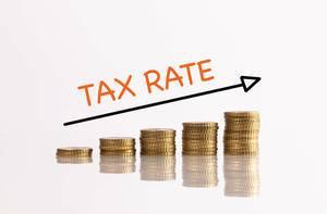 """Stapel aus Münzen mit Pfeil und dem Text """"Tax Rate"""" (Steuersatz)"""