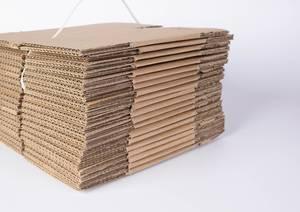 Stapel noch nicht gefalteter Kartonschachteln für Umzug oder Lagerung vor weißem Hintergrund