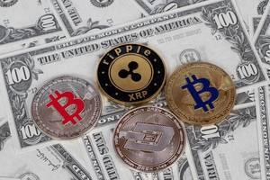 Stapel von Kryptowährungen liegen auf Banknoten