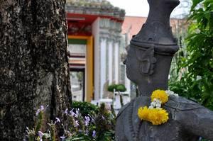 Statue mit Blumen über der Schulter in der Nähe des Tempels Wat Po