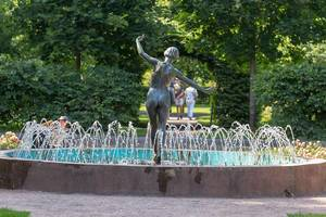 Statue of woman with naked butt in the middle of a round fountain in a park