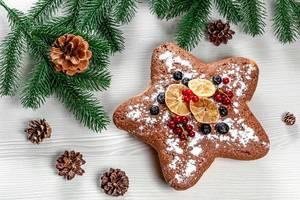 Sternförmiger Biskuitkuchen mit roten Johannisbeeren, Heidelbeeren und getrockneten Zitrusfrüchten, Aufnahme von oben mit Weihnachtsdeko