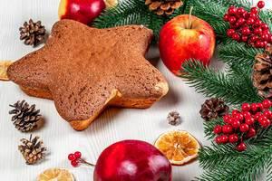 Sternförmiger Kuchen auf dem Tisch mit Äpfeln, getrockneten Zitrusfrüchten und Weihnachtsdeko