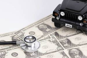 Stethoscope and black car on dollar banknotes