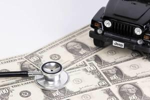 Stethoskop und schwarzer Spielzeug-Jeep auf US-Dollar-Scheinen