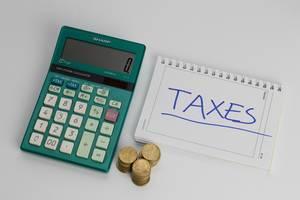 Steuerberechnung - TAXE auf einem Notizblock mit Münzen und einem Taschenrechner
