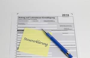 Steuererklärung 2018: Unausgefüllter Lohneteuer-Antrag unter Notizzettel und blauen Kugelschreiber - Nahaufnahme in Draufsicht