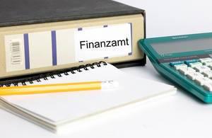 Steuererklärung - Ein Aktenordner auf den Finanzamt steht mit einer Taschenrechner, einem Notizblock und einem Bleistift