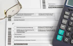 Steuererklärung für das Finanzamt mit Brille und Taschenrechner