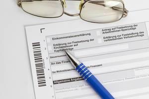 Steuererklärung mit einem Kugelschreiber und einer Brille