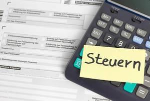 Steuern machen - Papierformular mit einem Taschenrechner und post it mit Steuern darauf