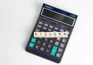 Steuern - the German word for taxes on top of a simple electronic calculator lying on a white surface