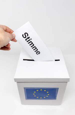 Stimmabgabe für die Europawahl mit einem Wahlschein und einer Urne mit Europaflagge
