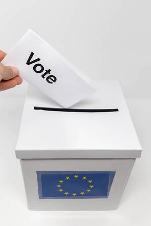 """Stimmzettel in einer Hand, ruft mit der Aufschrift """"Vote"""" zum Wählen gehen auf, während der Wahlschein in die Abstimmungsurne gesteckt wird"""