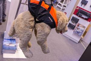 Stoffhund trägt orange-schwarze Schwimmweste für Hunde von Baltic und hängt an Haltegriff