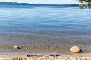 Strandabschnitt der Bucht der Insel Kelvenne in Finnland, mit Blick auf Steine im blauen See und Päijänne Nationalpark im Hintergrund
