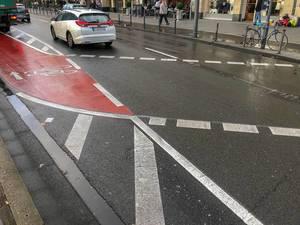 Straße mit abgetrenntem Fahrradweg, der die Straße kreuzt