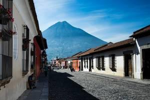 Straße mit typischen bunten Häuserfassaden in Antigua, Guatemala vor dem Volcan de Agua
