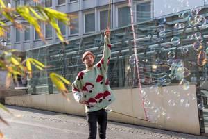 Straßenkünstler macht viele Seifenblasen