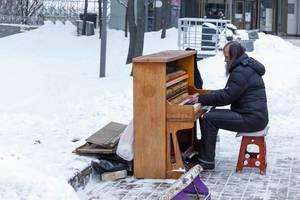 Straßenmusiker spielt auf Piano im Schnee in der Stadt