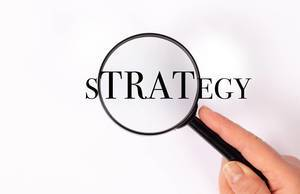 Strategy unter der Lupe auf weißem Hintergrund