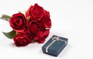 Strauß rote Rosen neben Geschenkbox mit silbernem Geschenkband vor weißem Hintergrund
