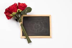 Strauß rote Rosen neben leerer schwarzer Kreidetafel vor weißem Hintergrund