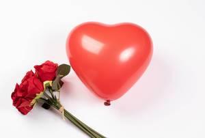 Strauß roter Rosen neben rotem Ballon in Herzform vor weißem Hintergrund