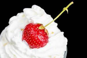 Strawberries with whipped cream on a dark background