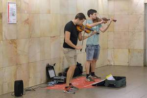 Street artist playing violins in Moscow Metro
