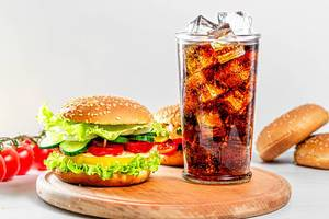 Street food concept - a glass of Coca Cola and hamburgers on a white wooden table