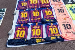 Street vendor sells Lionel Messi FC Barcelona soccer jerseys and Kylian Mbappé Merchandise at a flea market in Spain