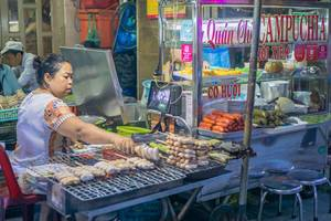 Streetfood Vendor selling grilled Bananas at a Market in Saigon