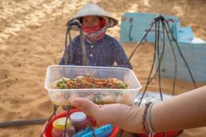 Streetfood vor einheimischer Verkäuferin bei roten Sanddünen in Mui Ne, Vietnam
