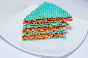 Stück eines süßen Kuchens aus bunten Waffeln und Kondensmilch vor weißem Hintergrund